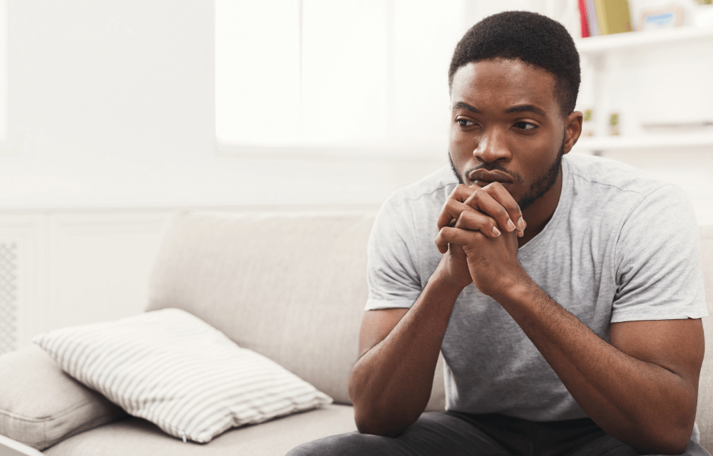A man sits on the couch with his hands clasped under his chin and looking contemplative