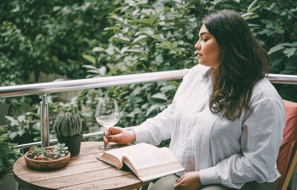 A woman in a larger body sitting on her balcony with a book and a glass of wine